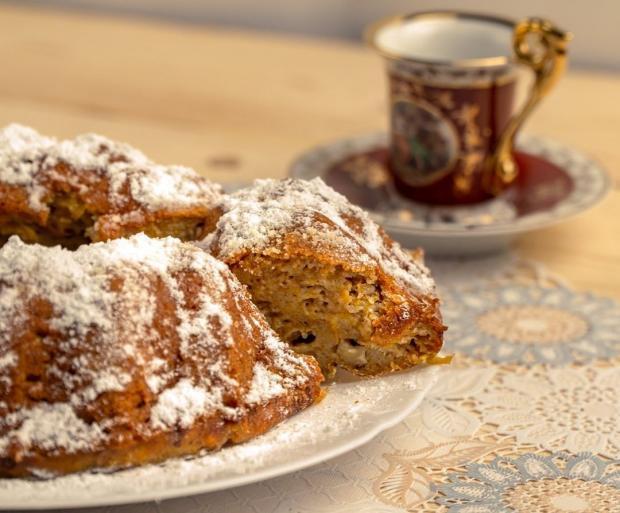 Манник на красивом блюде стоит на столе возле чашки с чаем