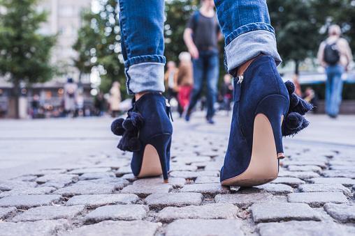 девушка идет по мостовой в джинсах и синих туфлях на высоком каблуке