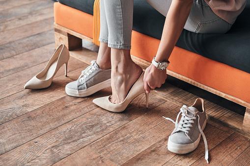 девушка примеривает перед покупкой в магазине туфли