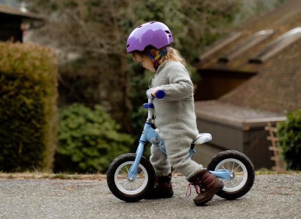 Маленькая девочка в сером комбинезоне на велосипеде