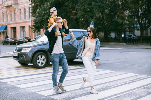 Молодой человек несет на плечах маленького ребенка и переходит дорогу с молодой женой