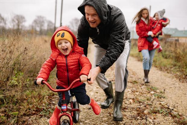 Мужчина в темной куртке ловит маленького ребенка