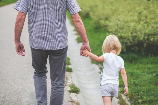 Мужчина ведет за руку маленького мальчика