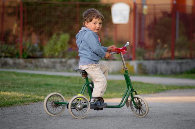 Маленький мальчик на трехколесном велосипеде