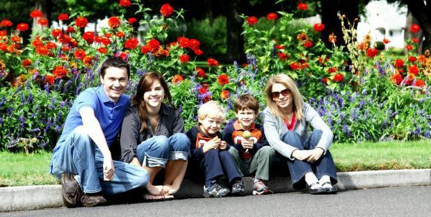 мама с детьми на фоне цветущих клумб