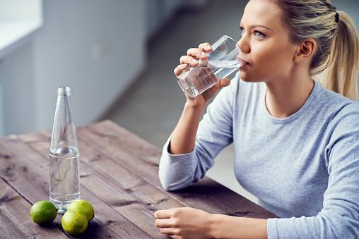 сидящая за столом девушка пьет газированную воду из стакана