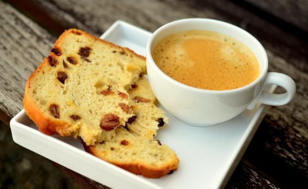 чашка кофе с ломтиком хлеба на белой квадратной тарелке