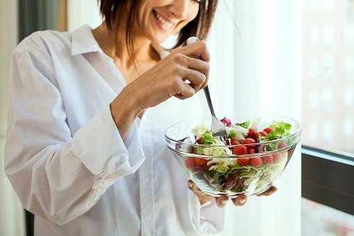улыбающаяся девушка в белой рубашке ест овощной салат