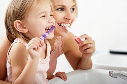 мама с  дочкой весело чистят зубы