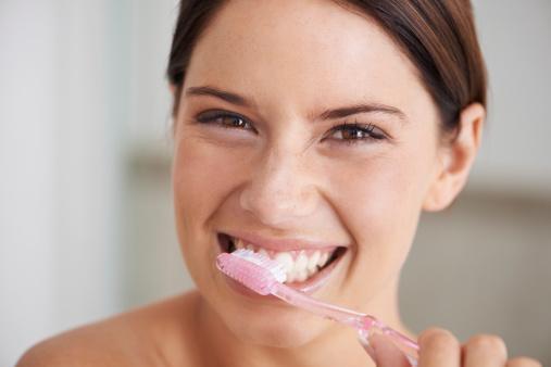 девушка с улыбкой чистит зубы