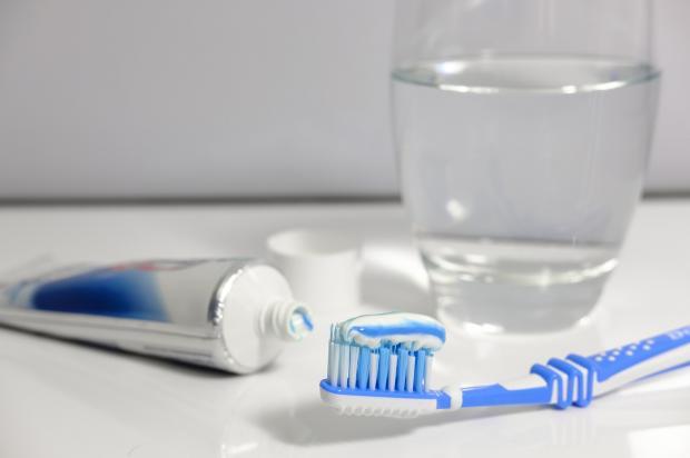 на столе стоит стакан воды с зубной пастой и щеткой