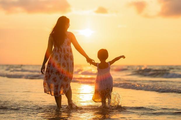 мама с дочкой в сарафанах идут по кромке моря