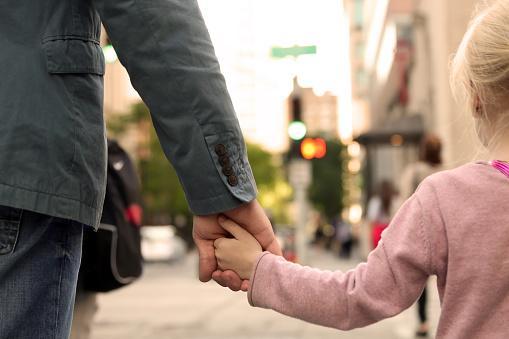 взрослый держит ребенка за руку при переходе через дорогу