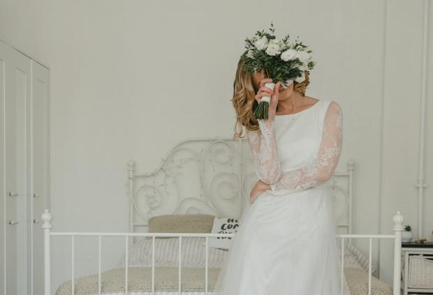 Девушка в свадебном платье прикрывает лицо букетом