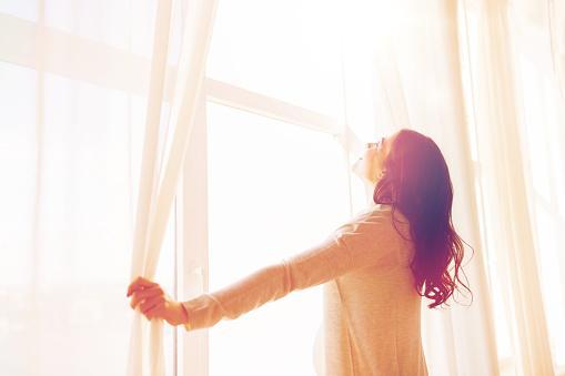 девушка раскрывает белые занавески на окне