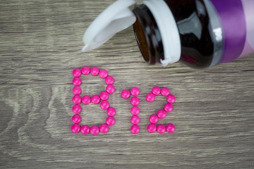 выложенная на столе из красных таблеток надпись витамин В12