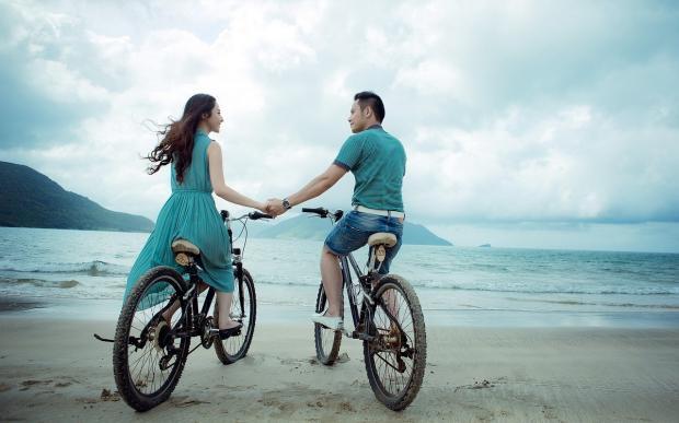 парень и девушка на берегу моря на велосипедах