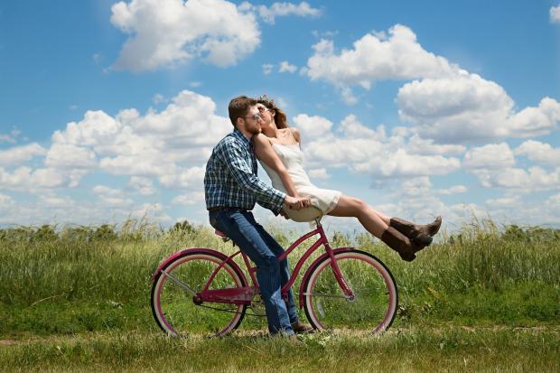 девушка с парнем едут на велосипеде