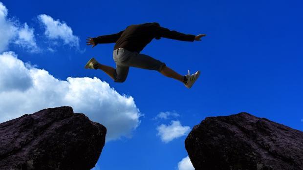человек прыгает с камня на камень через пропасть