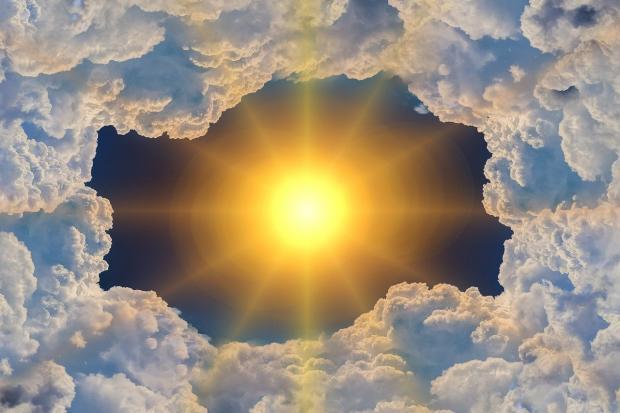 яркое солнце проглядывает  сквозь кучевые облака