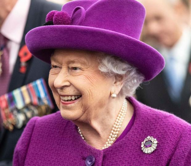 королева Великобритании Елизавета II в фиолетовом наряде и шляпке