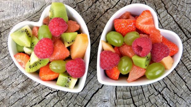 две тарелки в форме сердца с ягодами и фруктами
