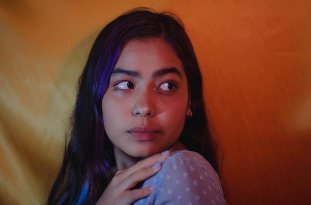 Темноволосая девушка смотрит через плечо
