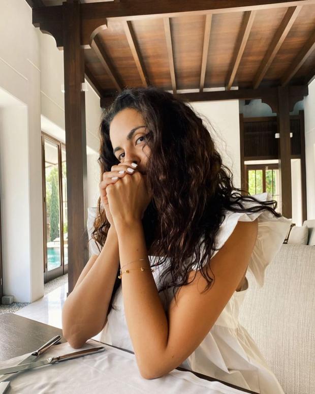 Настя Каменских с распущенными волосами и в белом платье сидит за столом