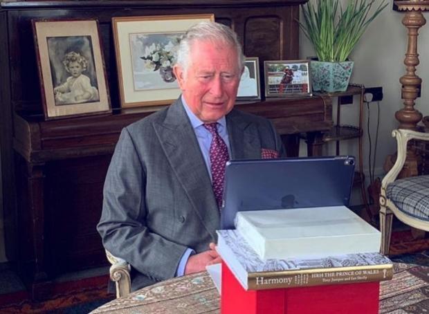 принц Чарльз сидит за столом и смотрит в ноутбук