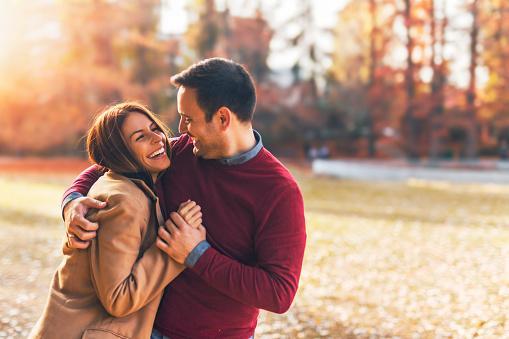 на фоне осеннего пейзажа мужчина и девушка смеются