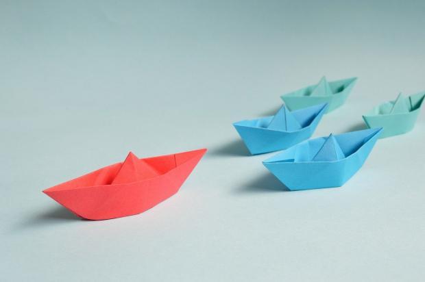 красный бумажный кораблик опережает синие