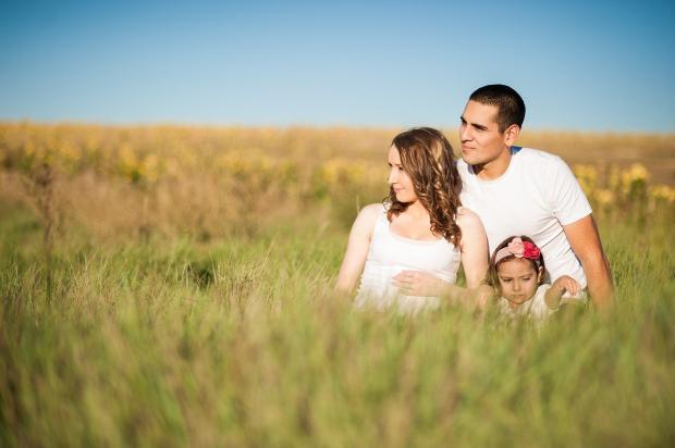 мама, папа и ребенок сидят в поле