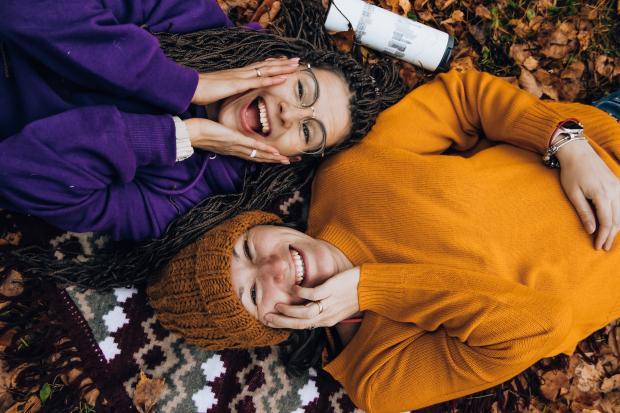 Две девушки в ярких свитерах лежат на земле