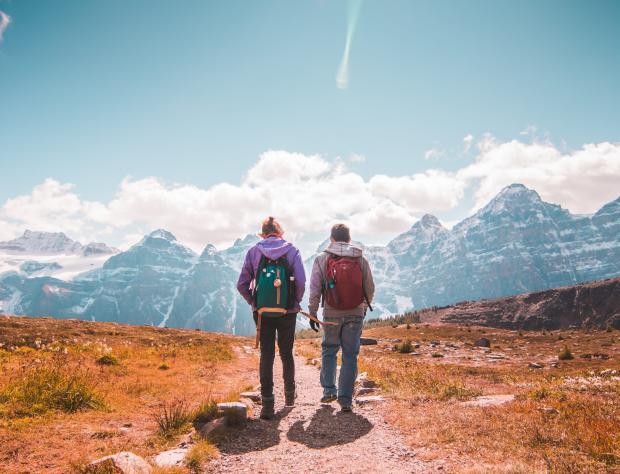 Двое мужчин с рюкзаками идут по тропинке в горах