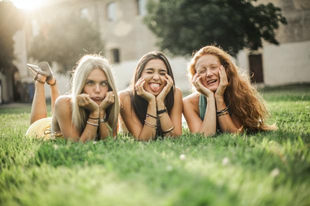 Три молодые девушки лежат на газоне и кривляются