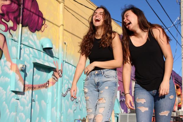 Две девушки в джинсах и черных майках смеются на улице