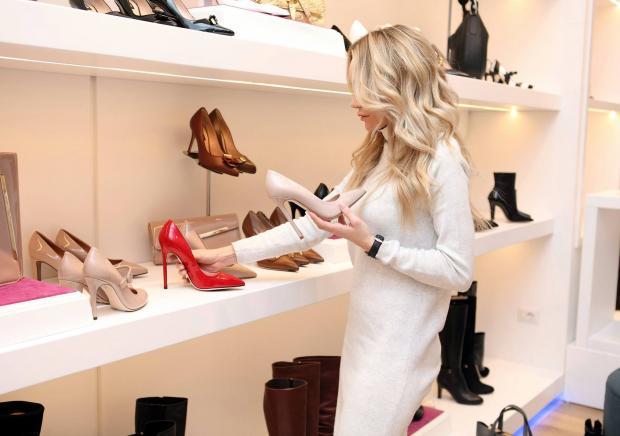 Девушка в белом платье выбирает туфли