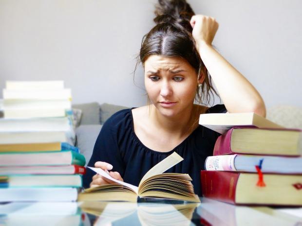 девушка сидит за стопкой книг