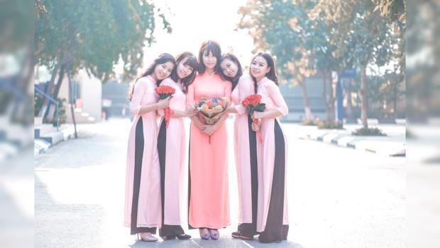 на улице стоят красивые двушки в длинных платьях с цветами