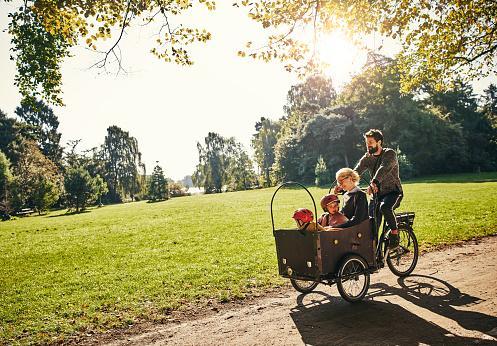 мужчина катит в велосипедной коляске несколько детей