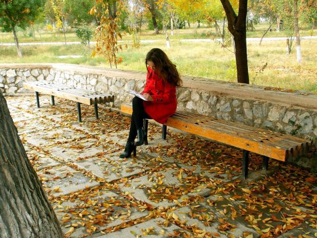 девука сидит в парке на скамейке