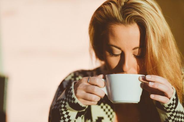 девушка с длинными волосами пьет кофе из белой чашки
