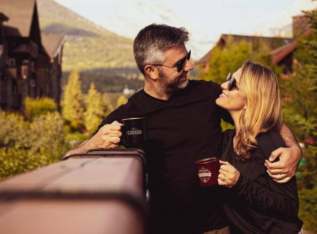 Мужчина в черной футболке держит в руке чашку и обнимает женщину в черном свитере