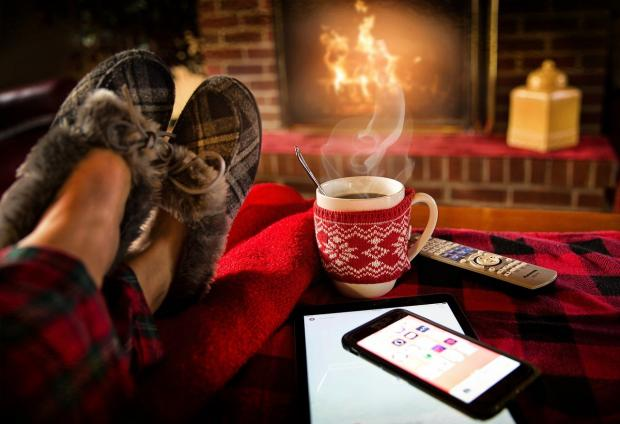 ноги человека перед горящим камином и кружка  с рождественской символикой