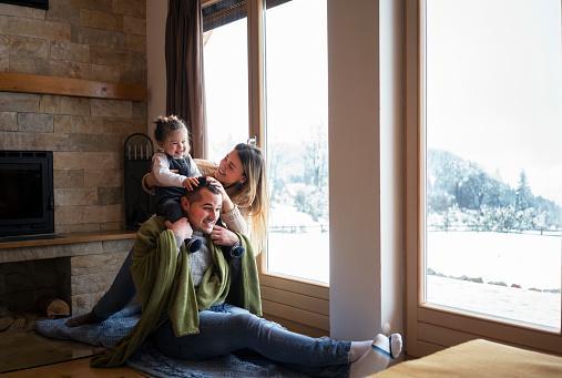 мама с папой и ребенком играют у большого панорамного окна