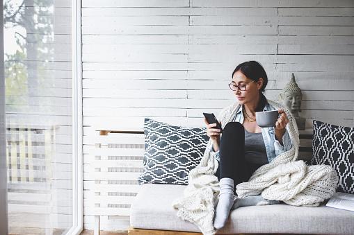 девушка на белом диване пьет чай с телефоном