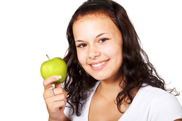 девушка с зеленым яблоком в руках