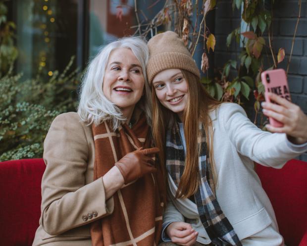 Молодая девушка сидит на скамейке со старшей женщиной и делает фото на розовый телефон