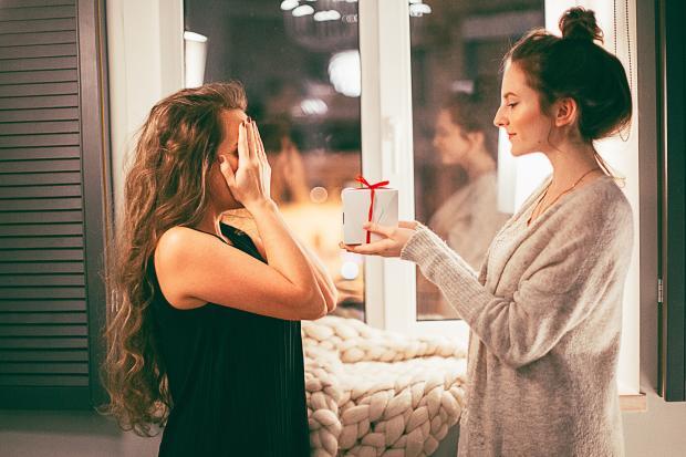 Молодая девушка делает подарок другой женщине