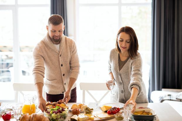 Молодой мужчина и женщина накрывают на стол